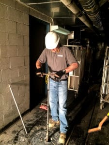 Farmer EG at work inside a building with pipes